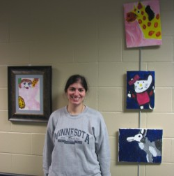 Jordina posing with her artwork at Achieve Services, Inc.